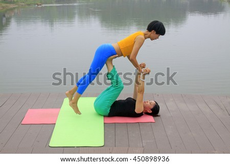 Luannan county - July 25: two women doing yoga exercise in the park, on July 25, 2015, luannan county, hebei province, China