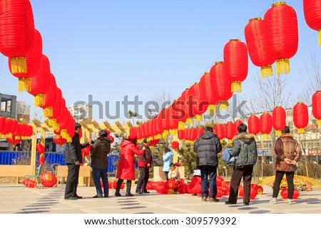LUANNAN COUNTY - MARCH 5: On the Lantern Festival Day, People were busy with hanging red lanterns in a park, March 5, 2015, luannan county, hebei province, China