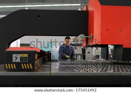 Luannan, November 24, 2012: A worker was operating CNC machine tools, in the DingRe Solar Energy Ltd, in November 24, 2012, Luannan County, china.   - stock photo