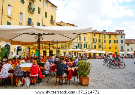 LUCCA, ITALY - AUGUST 19, 2014:People sitting by restaurants at the city center  - stock photo