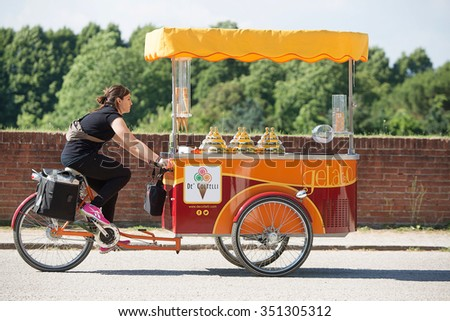 Lucca, Italy-June 7, 2015. Ice Cream Vendor riding her tricycle cart on top of the wall surrounding the ancient city of Lucca, Italy