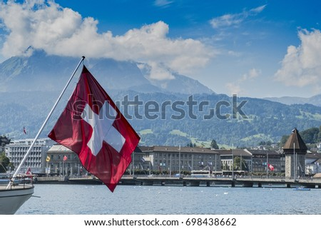 LUCERNE, SWITZERLAND - AUGUST 13, 2017: Cityscape of Lucerne with huge swiss flag in the foreground
