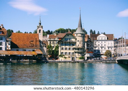 LUCERNE, SWITZERLAND - CIRCA AUGUST 2011: Buildings along the river Reuss in Lucerne, with the famous Chapel Bridge, the oldest wooden covered bridge in Europe, in the foreground.