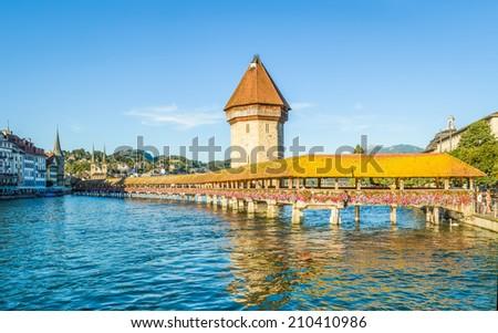 LUCERNE, SWITZERLAND - JULY 18, 2014: Chapel Bridge, swans and Jesuit Church, Lucerne. The wooden covered bridge spans the Reuss River - stock photo