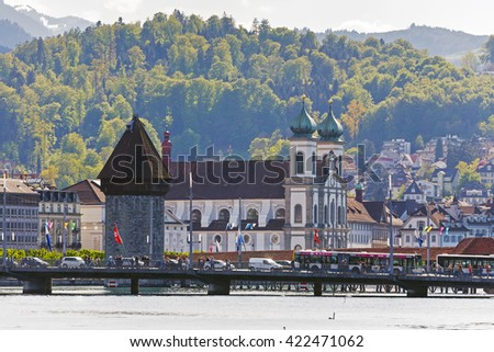 LUCERNE, SWITZERLAND - MAY 04, 2016: Early evening view towards the Jesuit Church located at the Reuss river bank and The World famous Watertower (Wasserturm) with its octagonal structure