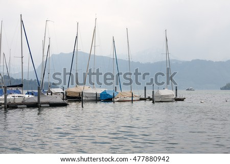 LUCERNE, SWITZERLAND - MAY 03, 2016: Moored sailboats can be seen in the small marina located along the promenade on the shore of Lake Lucerne. This is shown during an overcast day.