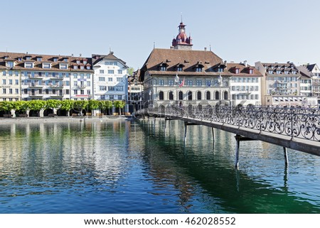 LUCERNE, SWITZERLAND - MAY 05, 2016: Pedestrian bridge leading to the right bank of the river Reuss, where can be seen the historic architecture with massive town hall and its tower
