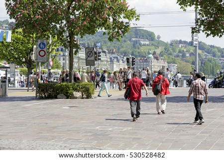 LUCERNE, SWITZERLAND - MAY 08, 2016: Street view of the city and a unidentified people who pass through pedestrian crossing and the others walk on sidewalk.