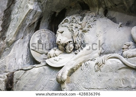 LUCERNE, SWITZERLAND - MAY 04, 2016: The monument of Dying Lion was carved in rock wall by the design of Danish artist Thorwaldsen. It is a World famous tourist attractions  - stock photo