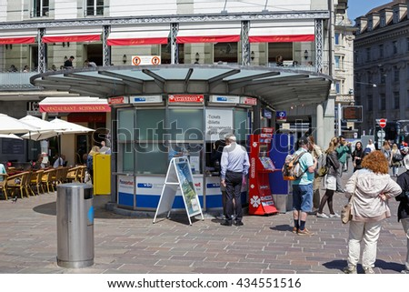 LUCERNE, SWITZERLAND - MAY 06, 2016: Unrecognized passers do some shopping at a kiosk offering a variety of tickets. Tickets sales in heavily used areas is very helpful for residents and tourists