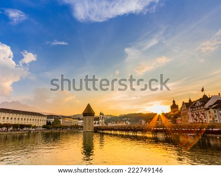 LUCERNE, SWITZERLAND - SEP 16, 2014: Sunset over river Reuss in Lucerne, Switzerland. It is a famous tourist destination due to its location on the shore of Lake Lucerne within sight of Swiss Alps. - stock photo