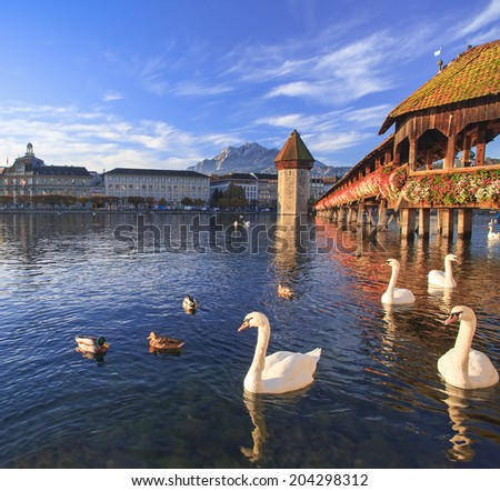 Lucerne, Switzerland - the Chapel Bridge (German: Kapellbrucke) and the Water Tower (German: Wassertum) with the Mt. Pilatus at the background in autumn early morning - stock photo