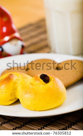 Lucia Bun and gingerbread biscuit with milk - stock photo