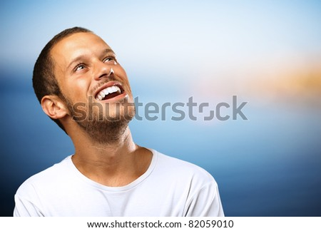 lucky boy laughing looking up against a beach background - stock photo
