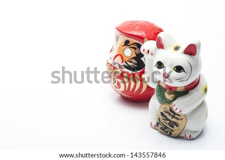 lucky cat and dharma on white background - stock photo