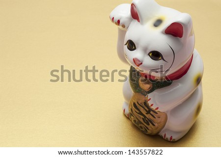 lucky cat on gold background - stock photo