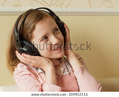 Lucky girl listens to music in the big headphones. - stock photo
