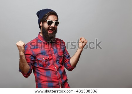 Lucky young hipster man isolated over grey background. Bearded man wearing glasses and hat acts like he won something with copy space - stock photo
