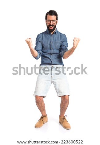 Lucky young hipster man over white background - stock photo