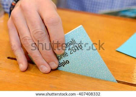Lugano, Switzerland - 11 april 2016: Hand putting a voting ballot in a slot of wooden box at the municipal election of Lugano on Switzerland - stock photo