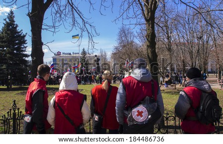 LUGANSK, UKRAINE - MARCH 30, 2014: Red Cross staff ready to help protesters.  Lugansk separatist rally gathered only about 500 people. All of them supported the calls to join Russia