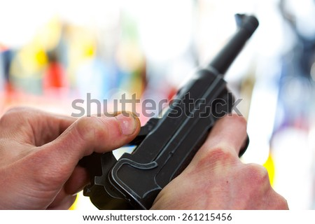 Luger automatic pistol in a human hand, shallow depth of field. close-up - stock photo