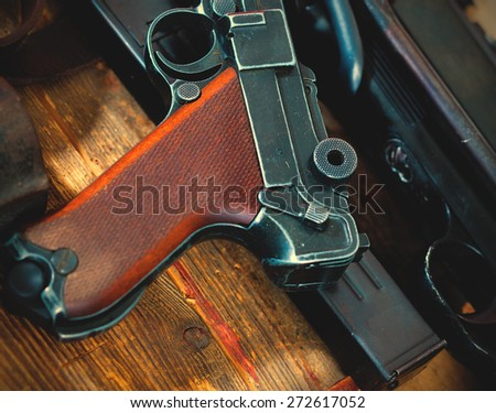 Luger Parabellum pistol and submachine gun MP 38 in gunsmith on table in a gunsmith. instagram image retro style - stock photo