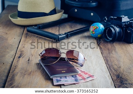 Luggage accessories passport and money on the wooden floor - stock photo