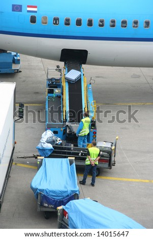 Luggage being unloaded from an airplane at the airport - stock photo