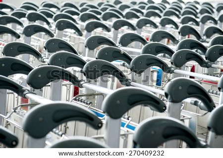 luggage carts at modern airport Close up view of trolleys luggage in a raw in airport - stock photo