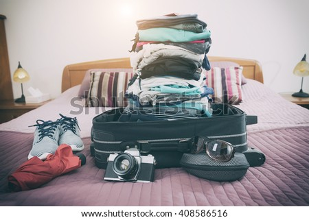Luggage with pile of clothes, camera, sunglasses and other items on bed - stock photo