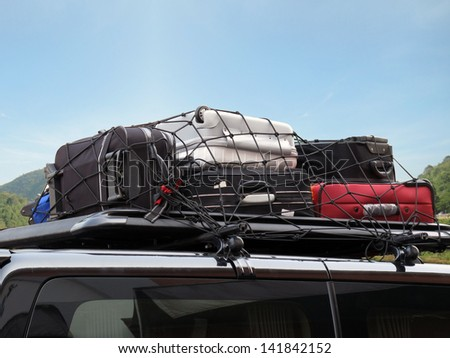 luggages over the car roof for a trip - stock photo