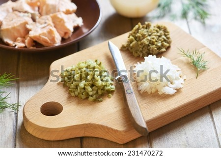 Lumaconi pasta with baked salmon, pickles and capers, italian cuisine. Cooking process. Step 3. Chopped ingredients - stock photo