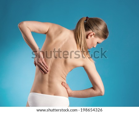 Lumbar vertebra. Young female suffering from spine ache touching her painful back over blue background.  - stock photo