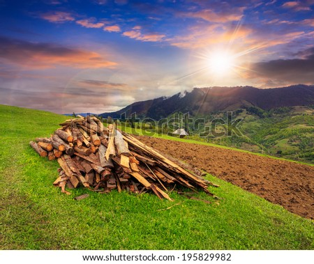 lumber and  wooden planks on agriculture field with  arable near village in mountains at sunset - stock photo