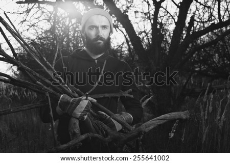 lumberjack cleans up in apple orchard with dry branches in his hands - stock photo