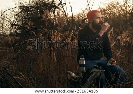 lumberjack eating homemade sandwich and drinking tea - stock photo