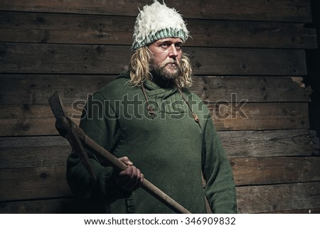 Lumberjack Winter Fashion Man Long Blonde Hair and Beard. Holding Pickaxe. Standing in Barn.