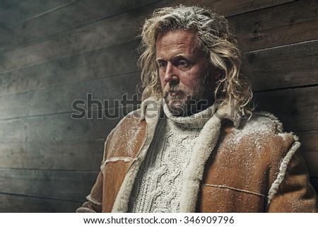 Lumberjack Winter Fashion Man Long Blonde Hair and Beard. Standing in Barn. - stock photo