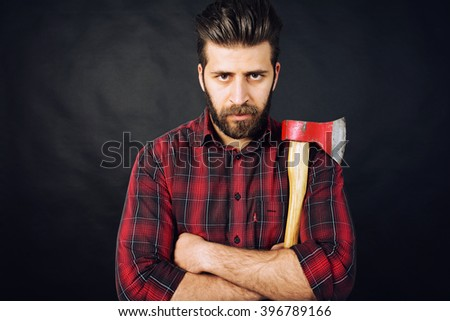 lumberjack with beard holding ax wearing red shirt. - stock photo
