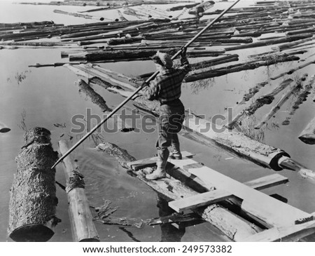 Lumberjill, a female lumberjack drives logs with pike pole during World War 2. The New Hampshire lumber mill was operated by women due to the absence of men in the military. Ca. 1944. - stock photo