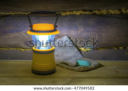Luminous hand lantern standing on the shelves near mitten and soap