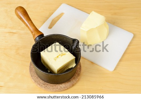 Lump of butter in cast iron pan and on plastic cutting board. - stock photo