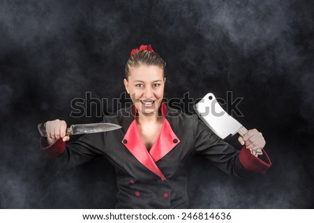 Lunatic maniac female chef holding knife and chopping knife with a smile on her face - stock photo