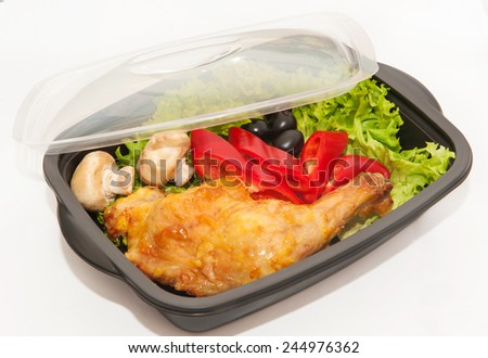 Lunch box with chicken thighs, peppers, mushrooms, olives and salad - stock photo