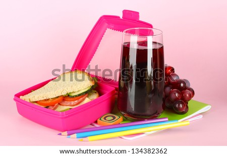 Lunch box with sandwich,grape,juice and stationery on pink background - stock photo