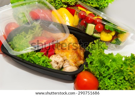 Lunch containers with vegetable salad and fried chicken  with lettuce - stock photo