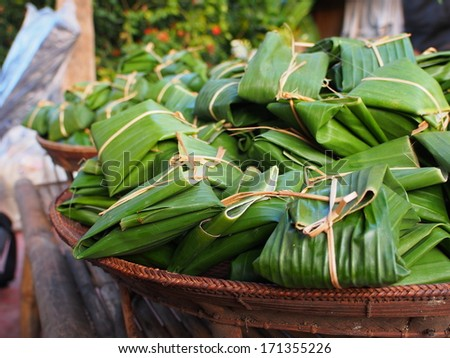 Lunch pack wrapped by banana leaf - stock photo