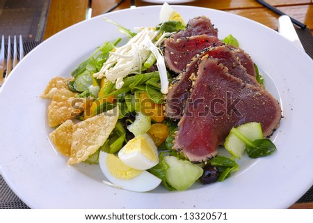 lunch salad with egg, mandarin, salad, sprouts, olives and steak tartar