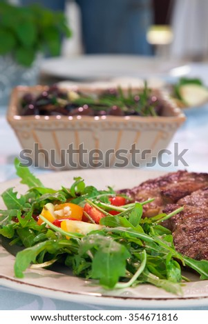 Lunch setting in the restaurant. Focus is foreground, on salad an steak in a plate, while olive salad is in the background. - stock photo